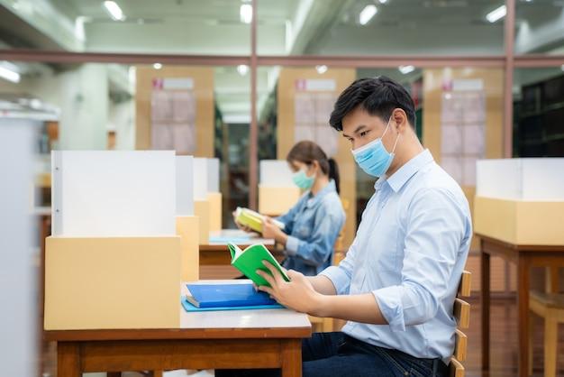 Dois estudantes asiáticos usando máscara facial e sentados na biblioteca a uma distância social de outros 6 pés