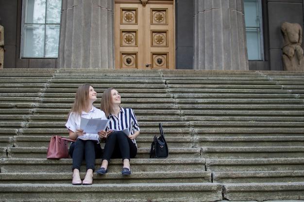 Dois estudantes atraentes sentam-se fora da universidade e dizem que estão aprendendo lições na escola