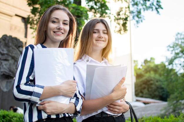 Dois estudantes bonitos estão de pé perto da universidade, segurando os papéis nas mãos e sorrindo na faculdade, eles vão para a escola