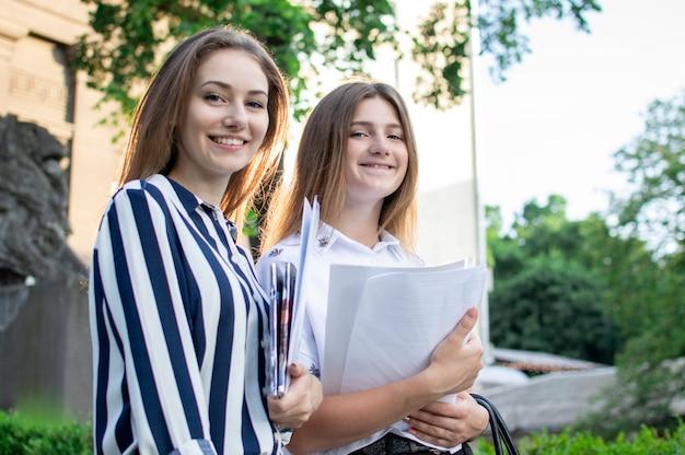 Dois estudantes bonitos estão de pé perto da universidade, segurando papéis nas mãos e sorrindo