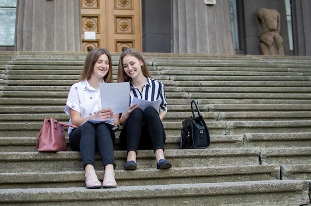 Dois estudantes bonitos sentam-se nos degraus perto da escola, seguram o papel nas mãos e aprendem lições, eles se comunicam na universidade durante o intervalo