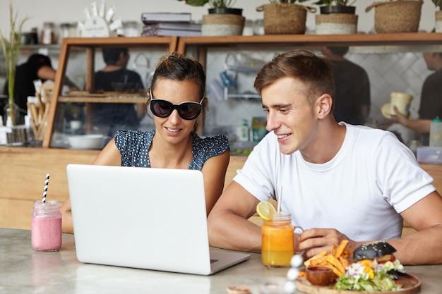 Dois estudantes conversando, desfrutando de conexão gratuita à internet sem fio, usando computador laptop, sentado à mesa com o notebook aberto, bebidas frescas e comida durante o intervalo do almoço