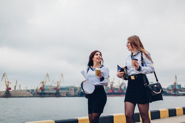 Dois estudantes das mulheres da faculdade da academia marinha que andam pelo uniforme vestindo do mar. amigos andando e apontando para a distância