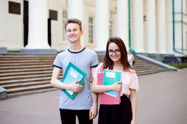 Dois estudantes exemplares em frente à antiga e bela universidade convencional