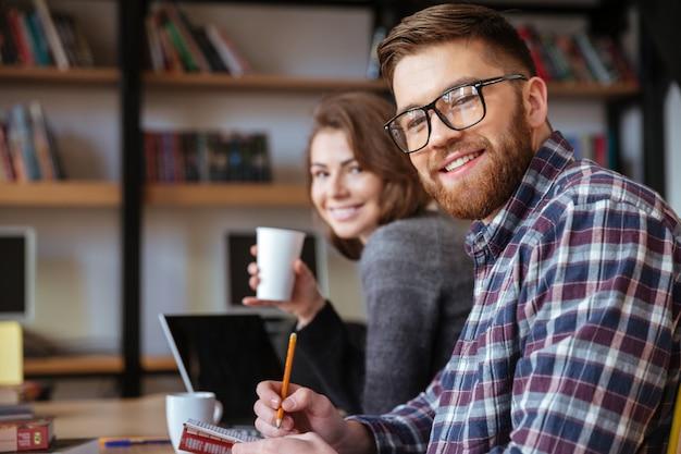 Dois estudantes felizes com redes de computadores laptop na biblioteca