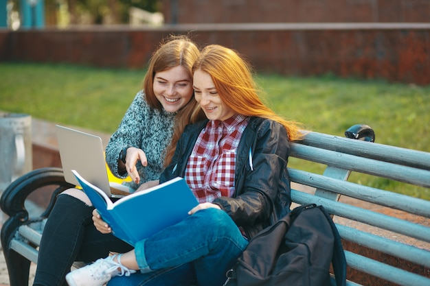 Dois estudantes sentam no banco olhando no livro e sorrindo