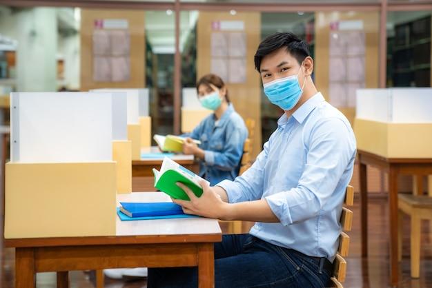 Dois estudantes universitários asiáticos usando máscara facial em uma biblioteca à distância social