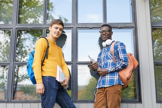 Dois estudantes universitários posando ao ar livre