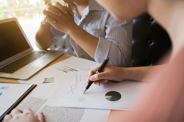 Dois estudantes universitários que trabalham em conjunto com documentos de laptop e exames em um café / biblioteca
