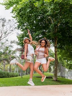 Dois, excitado, mulheres jovens, segurando, mapa, e, câmera, em, mão, pular ar