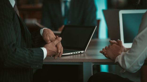 Dois executivos adultos conversando, sentados à mesa com laptops em um