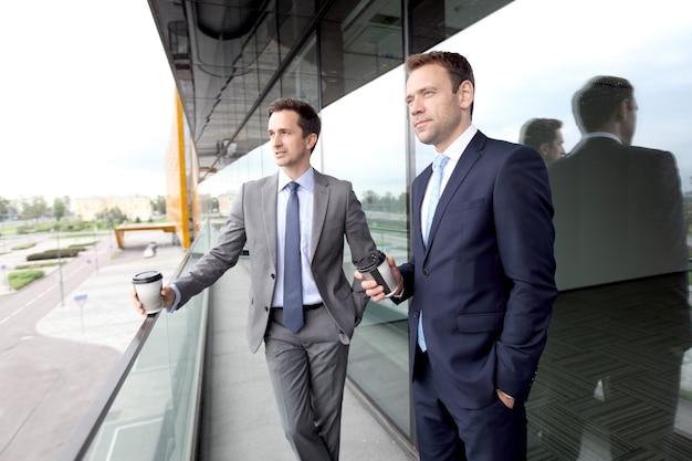 Dois executivos conversando com café na varanda de um prédio comercial