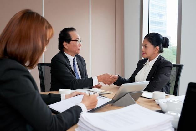 Dois executivos de negócios cumprimentam para fechar o acordo, enquanto o secretário está protocolando a ata da reunião