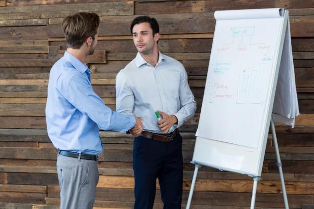 Dois executivos de negócios masculinos, apertando as mãos