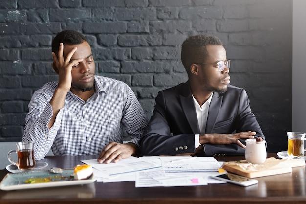 Dois executivos de pele escura em trajes formais parecendo deprimidos após terem fracassado em um negócio lucrativo