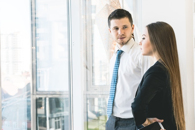 Dois executivos de terno conversando perto de grandes janelas