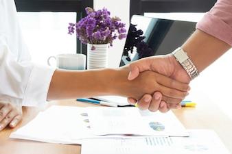 Dois executivos que agitam as mãos no escritório.