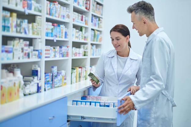 Dois farmacêuticos experientes escolhendo um medicamento farmacêutico para um cliente