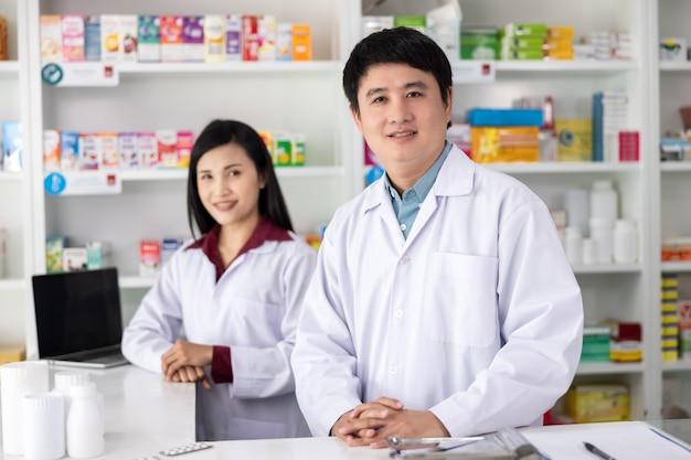 Dois farmacêuticos masculinos e femininos sorrindo felizes para o serviço na drogaria