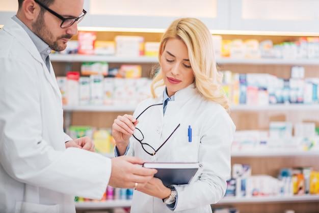 Dois farmacêuticos novos que verificam o inventário das medicinas na farmácia do hospital.