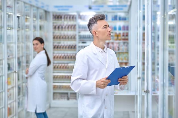 Dois farmacêuticos realizando a inspeção de rotina de todos os estoques de drogas