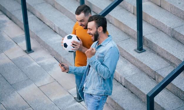 Dois fãs felizes e entusiasmados em clima de euforia após ganhar em uma aposta com um smartphone na mão ao ar livre