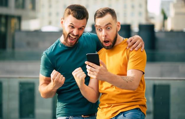 Dois fãs felizes e entusiasmados em clima de euforia após ganhar em uma aposta com um smartphone na mão