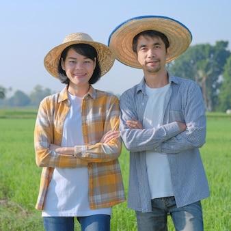 Dois fazendeiros asiáticos em pé e de braços cruzados em uma fazenda de arroz verde. conceito de alguns fazendeiros.