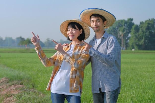 Dois fazendeiros asiáticos sorriem e fazem pose de dedo apontando para uma fazenda verde