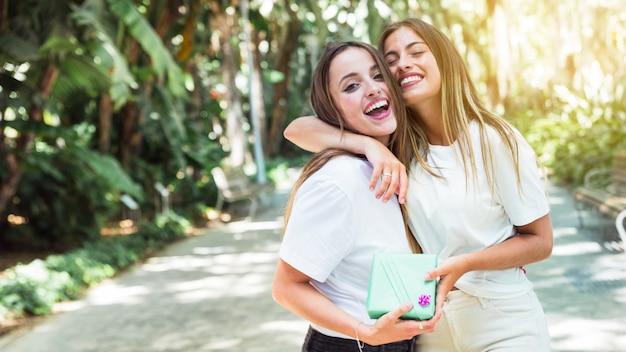 Dois, feliz, amigos, com, caixa presente, abraçando, um ao outro