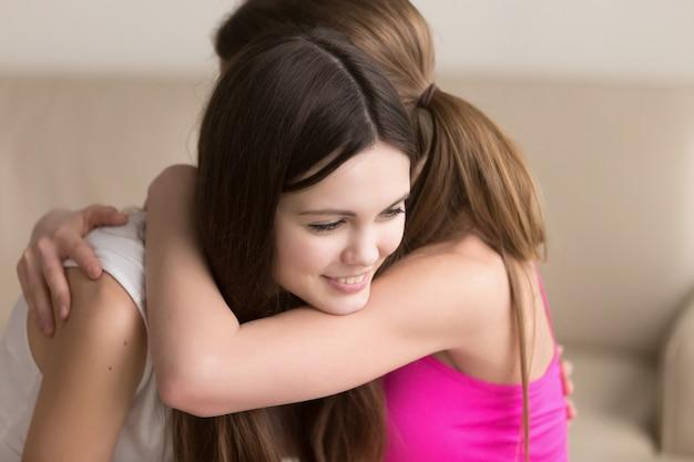 Dois, feliz, mulheres jovens, abraçando, quando, reunião