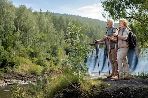 Dois felizes mochileiros maduros em trajes esportivos de pé à beira do rio da floresta enquanto observam a bela natureza durante a viagem