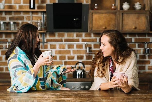 Dois, femininas, amigos, bebendo, xícara café, em, cozinha