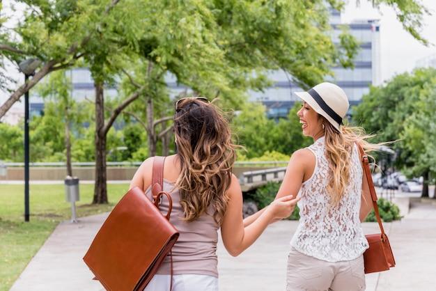 Dois, femininas, amigos, carregar, seu, bolsas couro, desfrutando, em, a, parque