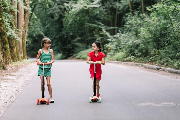 Dois, femininas, amigos, com, scooters, olhando um ao outro, ligado, estrada