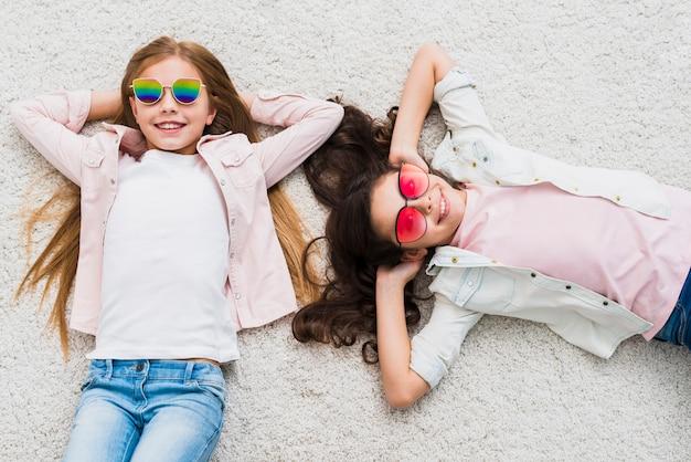 Dois, femininas, amigos, desgastar, elegante, óculos de sol, mentindo, branco, tapete
