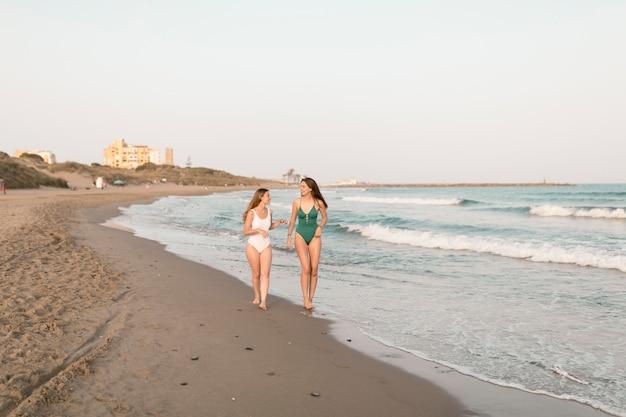 Dois, femininas, amigos, em, biquíni, andar, perto, a, seacoast, em, praia