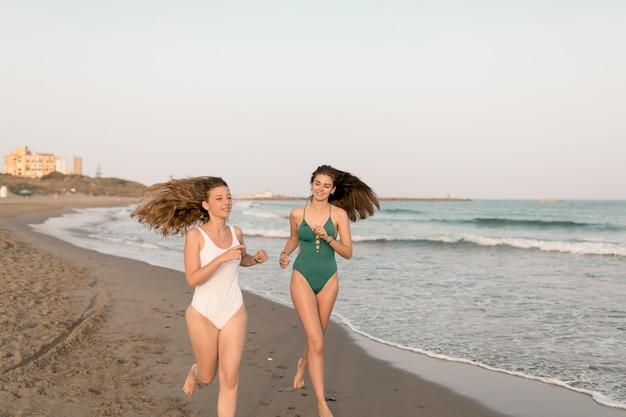Dois, femininas, amigos, executando, praia arenosa