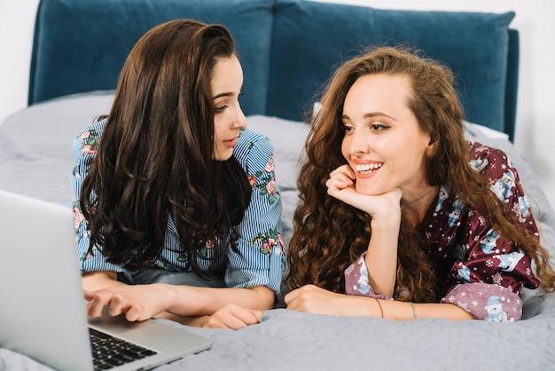 Dois, femininas, amigos, mentindo cama, com, laptop