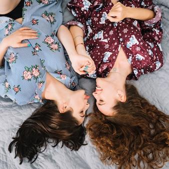 Dois, femininas, amigos, mentindo cama, segurando, cada, outro, mão