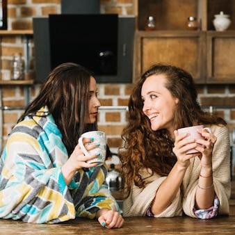 Dois, femininas, amigos, olhando um ao outro, enquanto, bebendo, xícara café