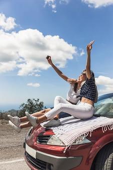 Dois, femininas, amigos, sentando, ligado, capuz carro, levando, selfie, através, cellphone