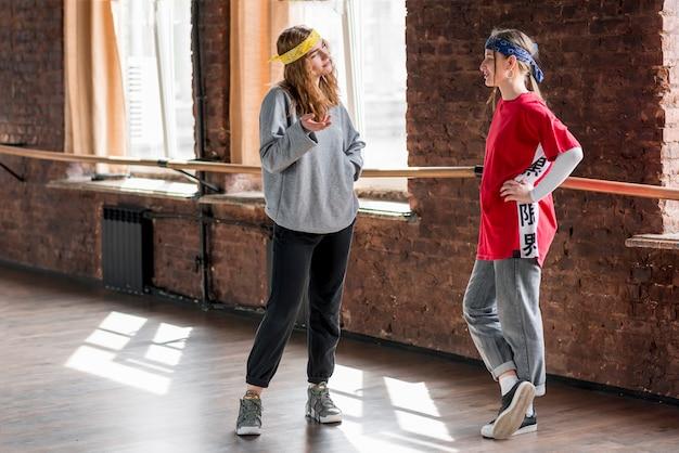 Dois, femininas, dançarino, ficar, em, estúdio, falando, um ao outro