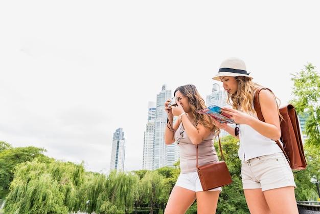 Dois, femininas, turista, levando, fotografia, de, câmera, e, dela, amigo, olhar, mapa