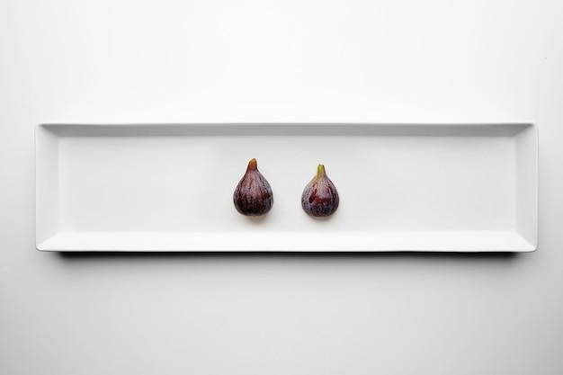 Dois figos isolados no centro da placa de cerâmica retangular na mesa branca