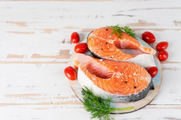 Dois filés de salmão cru com tomate na mesa de madeira