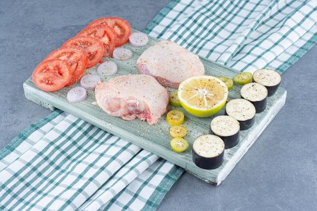 Dois filetes de frango e legumes fatiados na placa de madeira.
