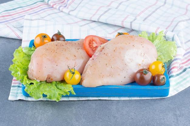 Dois filetes de frango na placa azul.