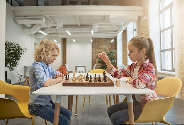 Dois filhinhos inteligentes, menino e menina, desenvolvendo estratégia de xadrez, jogando jogo de tabuleiro sentados