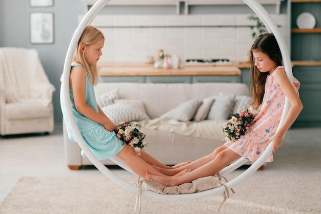 Dois filhos adoráveis em vestidos bonitos, sentado no balanço no quarto interior